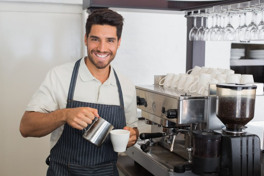 Waiter smiling and making cup of coffee at coffee shop